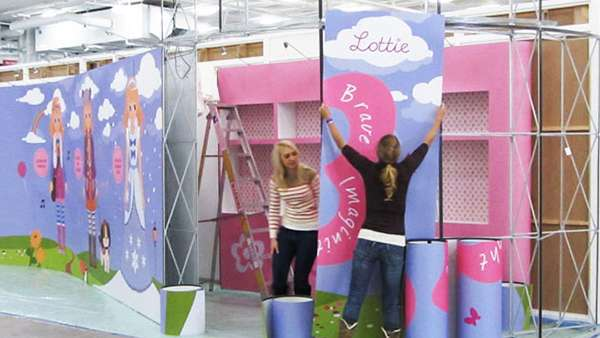 Chloe and Liana fitting graphics on exhibition stand
